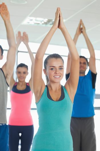 Portrait of fitness class and instructor with hands joined at exercise studio