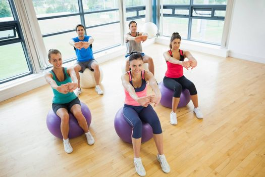 Portrait of smiling young people sitting on exercise balls and stretching out hands in the bright gym