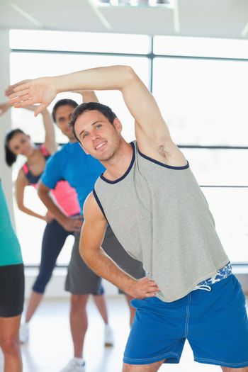 Portrait of sporty people doing power fitness exercise at yoga class