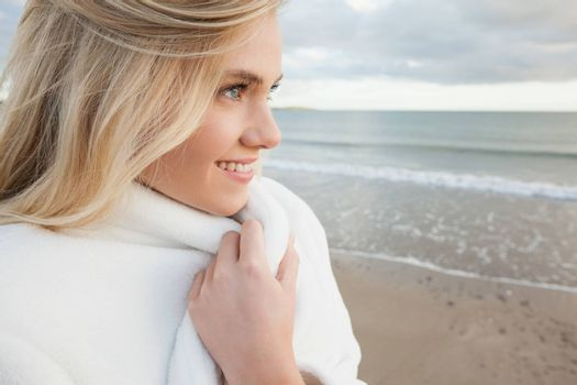 Close up of a cute smiling woman in stylish white jacket on the beach