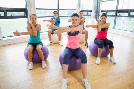 Portrait of smiling young people sitting on exercise balls and stretching hands in the bright gym
