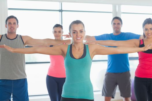 Portrait of sporty people stretching out hands at yoga class in fitness studio