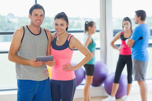 Fit couple holding digital table with friends chatting in background in bright exercise room