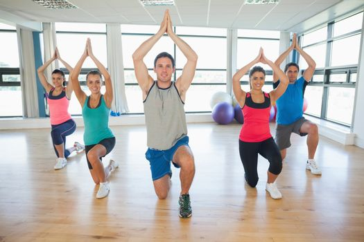 Fitness class and instructor kneeling in Namaste position at exercise studio