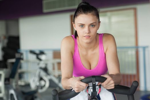 Portrait of a determined young woman working out at spinning class in gym