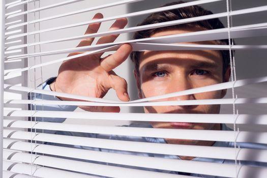 Businessman peeking through blinds