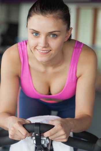 Portrait of a smiling young woman working out at spinning class in gym