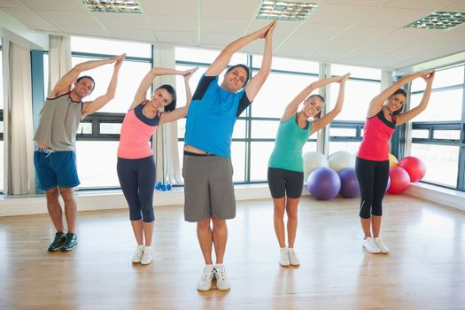 Fitness class and instructor standing in Namaste position at exercise studio