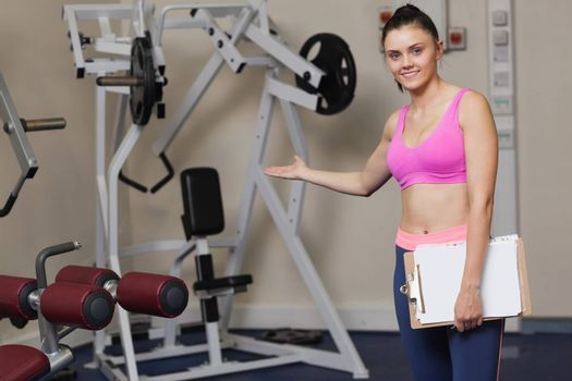 Portrait of a smiling female trainer with clipboard pointing toward the lat machine in the gym