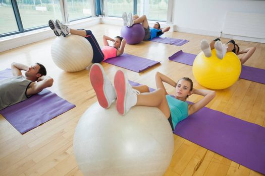 High angle view of class exercising with fitness balls at a bright gym