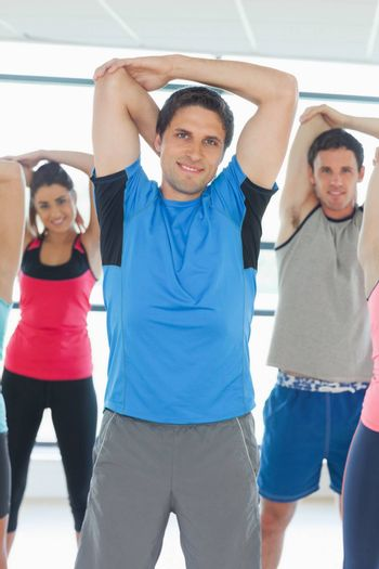 Portrait of sporty people stretching hands at yoga class in fitness studio