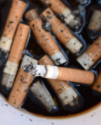 Ashtray Full of Cigarettes burnt butts wet and disgusting