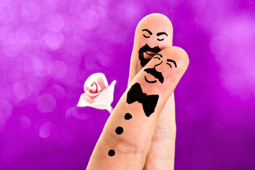 Fingers with sweet faces painted featuring a gay wedding between a man with a moustache and a bowtie and a guy with a beard an a rose