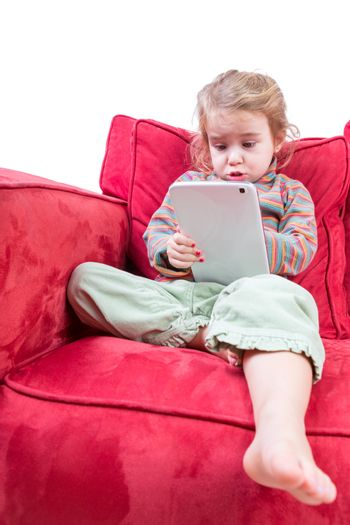 Cute little girl sitting on a sofa with a tablet