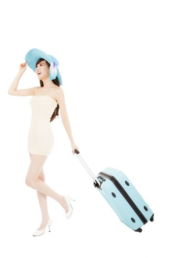 Fashionable woman running with suitcase