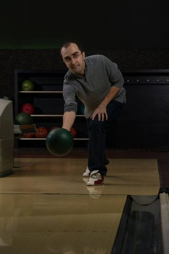 Smiling Young Man Playing With A Bowling Ball