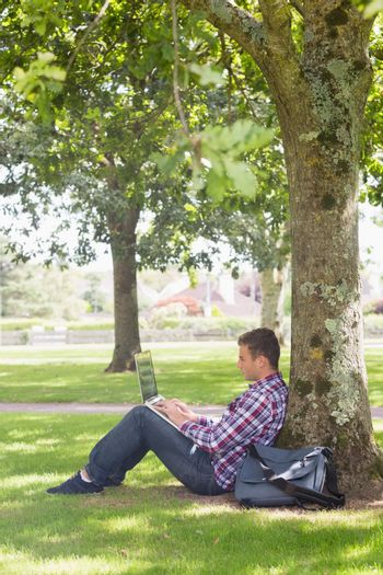 Young student using his laptop outside