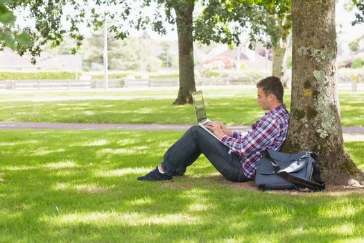 Young student using laptop outside
