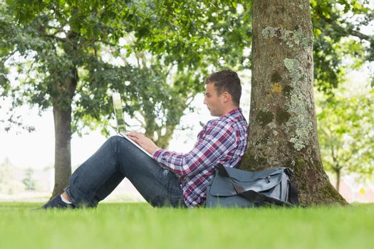 Young student using his laptop to study outside