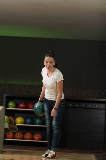 Young Women Playing With A Bowling Ball