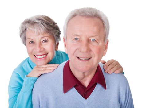 Portrait Of Senior Couple Enjoying Piggyback Isolated On White Background