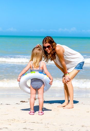 Mother and her daughter having fun on tropical beach.