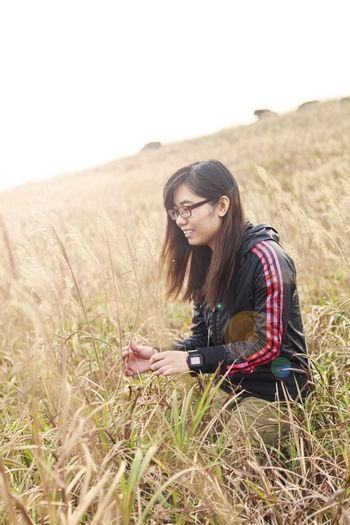 Asian woman in sunset grasses