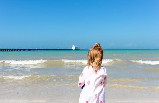 one Little girl staring at the ocean on a Yucatan beach