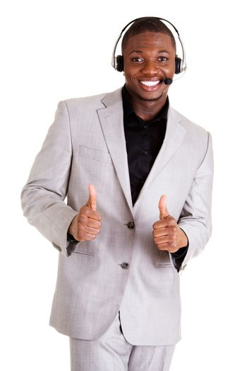 Charming customer service representative with headset on gesturing thumbs up.