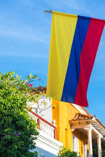 View of the Colombian flag with colonial architecture and blue sky in Cartagena, Colombia