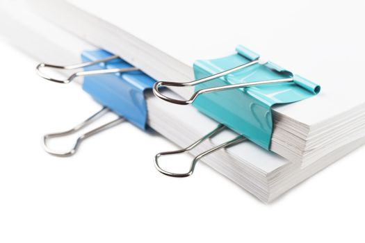 Closeup view of blue metal clips on white paper