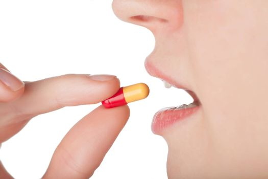 Woman taking a pill isolated over white background