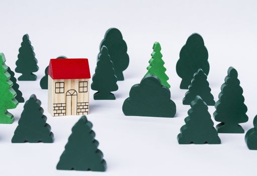 simple toy house in forest made of several trees. Grey background
