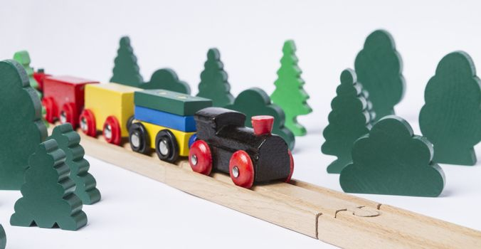 black wooden toy train in rural landscape made with simple toy trees