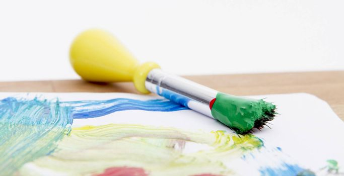 green paint with paint brush  and paper on wooden table
