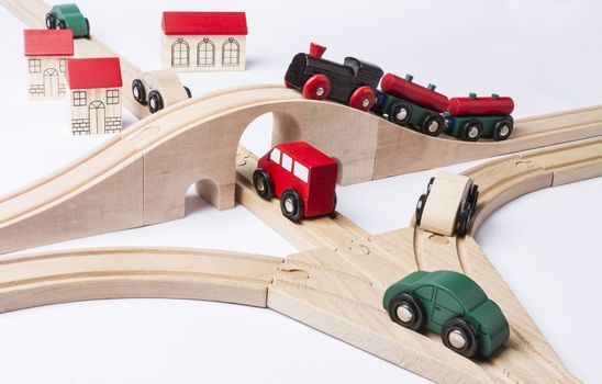 heavy traffic near small toy town. train on bridge and some cars