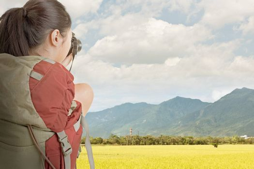 Young backpacker travel and take picture at rural with golden paddy farm under sky in Taiwan.