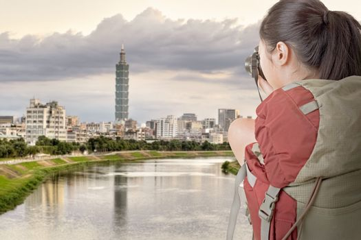 Young backpacker travel and take picture, the tower is the famous landmark, 101 skyscraper, Taipei, Taiwan.
