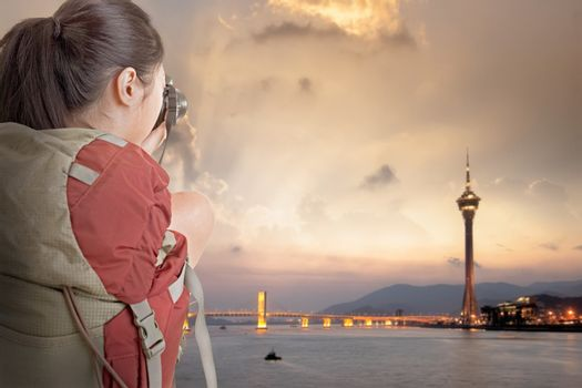 Young backpacker travel and take picture at Macau with famous travel tower.