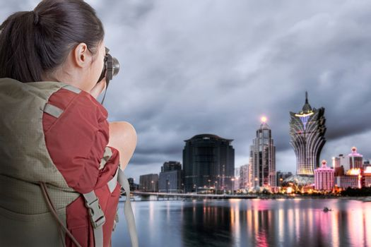 Young backpacker travel and take picture at Macau with famous casino skyscrapers.