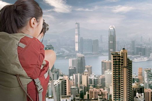 Young backpacker travel and take picture at Hong Kong with famous skyscrapers in daytime.