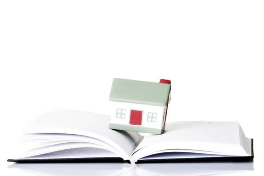 House standing on an open book. Isolated on white.