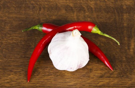 Two chili peppers lying with garlic.