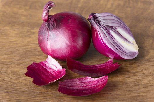 Red raw onion sliced into two. over wooden background.