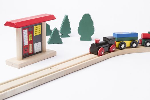 toy ticket machine at wooden railroad track with some trees in background