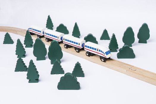 fast train driving through small forest. scenery made of wooden toy