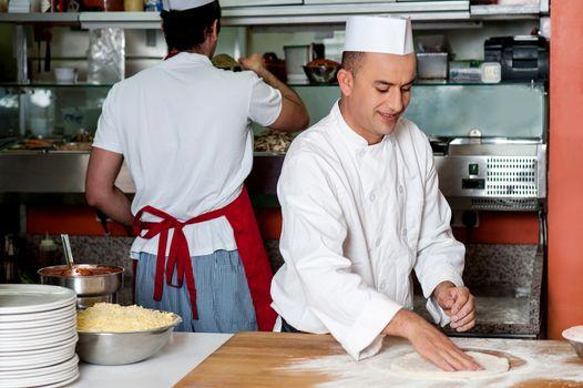 Chef preparing pizza base