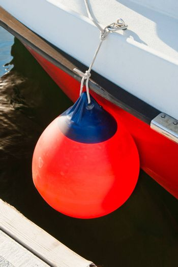 Round buoy with a monolithic eye at a board of the moored yacht
