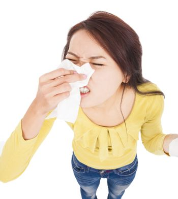 Young woman having  allergy and  blowing into tissue