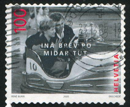 SWITZERLAND - CIRCA 2005: stamp printed by Switzerland, shows Man and woman in bumper car by Rene Burri, circa 2005